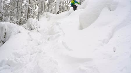 traumatic : Extreme snowboarder riding fresh powder snow down the steep mountain slope. Slow motion