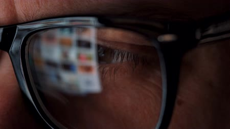 navegar : Man in glasses looking on the monitor and surfing Internet. The monitor screen is reflected in the glasses