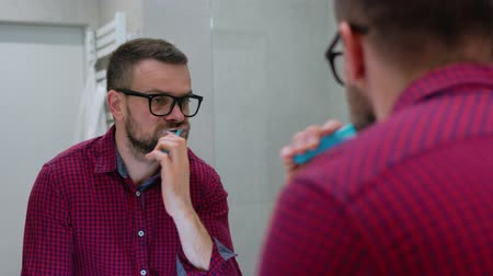 щеткой : Bearded man brushing his teeth in a bathroom in the morning. Morning hygiene.
