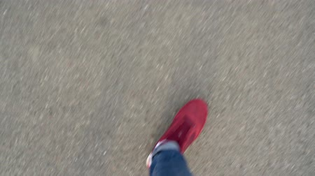 grey : Top view of mens legs in red sneakers walking on asphalt
