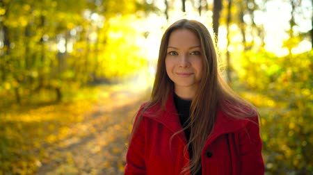 Portrait of a beautiful pensive girl in a red coat with a yellow maple leaf in the background in the autumn forest Stock Footage