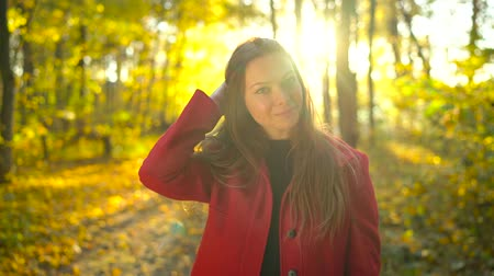 Portrait of a beautiful pensive girl in a red coat with a yellow maple leaf in the background in the autumn forest. Slow motion Stock Footage