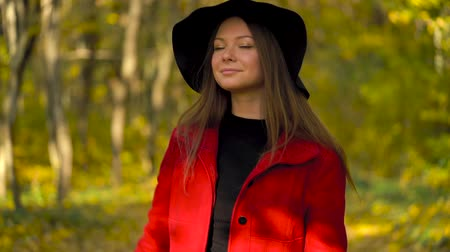 mutlu : Beautiful smiling girl in a black hat with a yellow maple leaf in the background walking in the autumn forest. Slow motion Stok Video