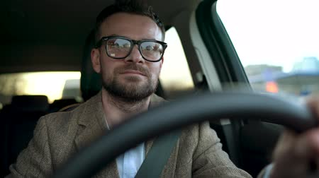 mutlu : Satisfied bearded man in glasses driving a car down the street in sunny weather Stok Video