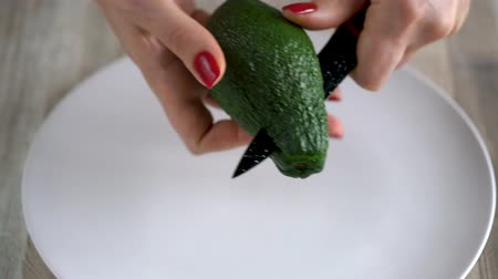fatia : Woman cuts avocado. The concept of modern healthy eating