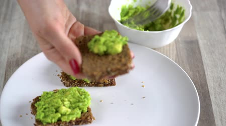 összetevők : Spreading mashed avocado on toast. Healthy vegan breakfast.
