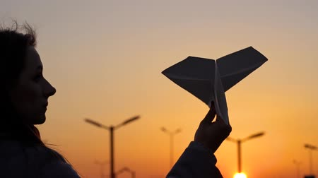asa : Woman launches paper airplane against sunset background. Concept of wanting to go on vacation or travel. Slow motion