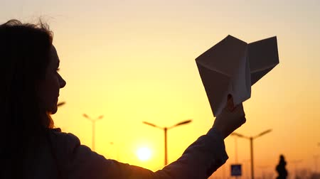 air vehicle : Woman launches paper airplane against sunset background. Concept of wanting to go on vacation or travel. Slow motion