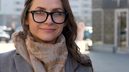 очки : Portrait of a woman in glasses with a hairstyle and neutral makeup on a city background closeup Стоковые видеозаписи