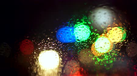 Close up rain drops on car window glass with blurred night city car lights bokeh as background