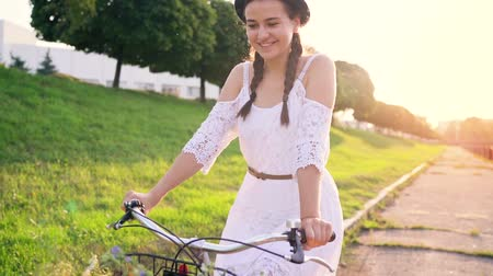 Young beautiful woman riding a bicycle at sunset
