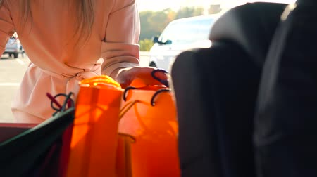 сумки : Beautiful girl puts shopping bags in the trunk of a car and leaves, intending to drive away. Slow motion.