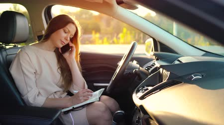 empresária : Business woman talking on a smartphone and taking notes in the dairy sitting in the car Stock Footage