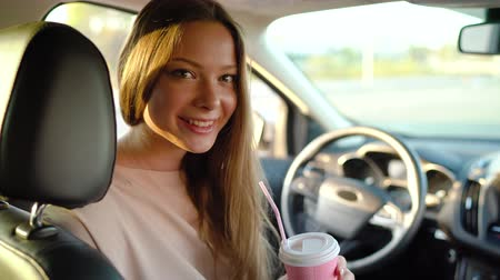 kierowca : Beautiful cheerful girl sits in the car, drinks coffee and laughs