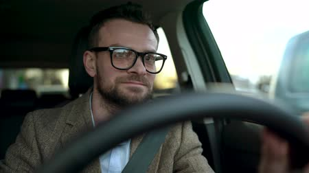 motoring : Satisfied bearded man in glasses driving a car down the street in sunny weather Stock Footage