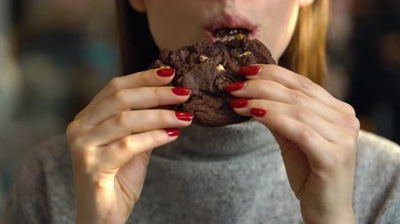 детали : Woman eats a chocolate chip cookies in a cafe