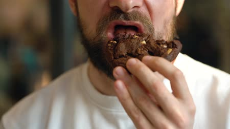 Man eats a chocolate chip cookies in a cafe