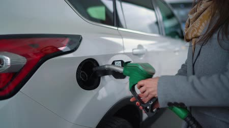 beczka : Woman fills petrol into her car at a gas station closeup