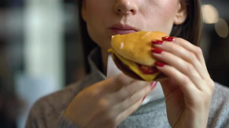 Woman eats a hamburger in a cafe
