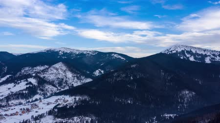 Hyper lapse of clouds running on blue sky over amazing landscape of snowy mountains and coniferous forest on the slopes Vídeos