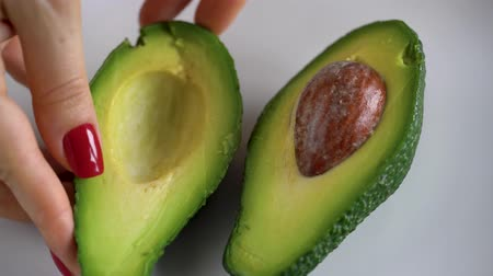 Woman opens avocado. The concept of modern healthy eating