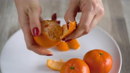 диеты : Womens hands peel the peel of tangerine, mandarin slices are piled on a plate