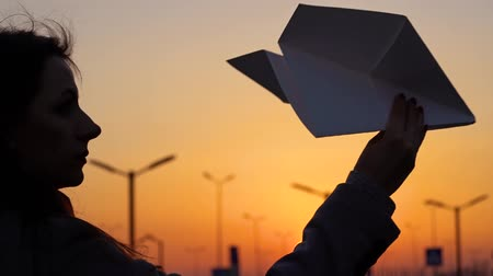 Woman launches paper airplane against sunset background. Concept of wanting to go on vacation or travel. Slow motion