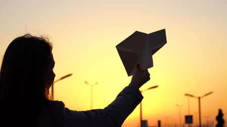 zabawka : Woman launches paper airplane against sunset background. Concept of wanting to go on vacation or travel. Slow motion