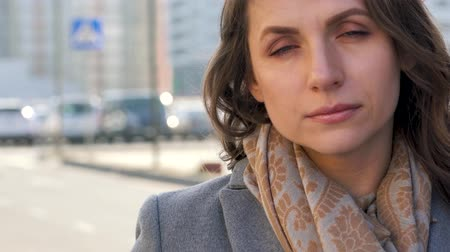 сияющий : Portrait of a woman with a hairstyle and neutral makeup on a city background closeup