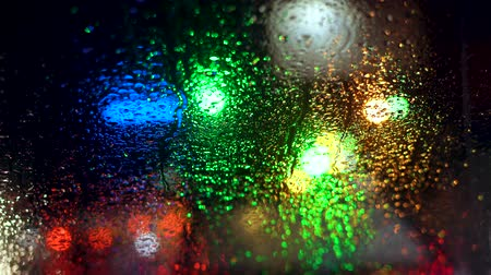 noc : Close up rain drops on car window glass with blurred night city car lights bokeh as background