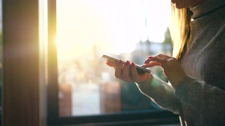 navegar : Female hands using smartphone against a blurred cityscape in the setting sun