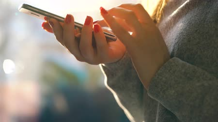 сообщений : Female hands using smartphone against a blurred cityscape in the setting sun