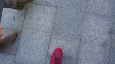 koronka : Top view of male legs in sneakers, which go along the sidewalk, meet female legs in boots and then walk together
