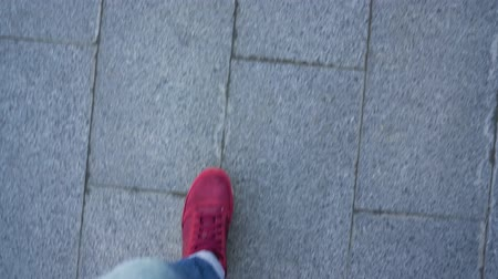 Top view of mens legs in red sneakers walking along the sidewalk