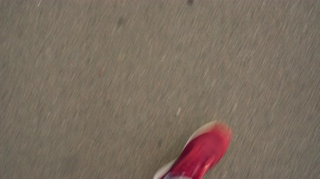 Top view of mens legs in red sneakers walking on asphalt