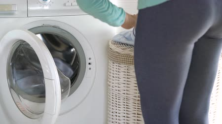 sıkıcı iş : Woman loads the laundry in the washing machine Stok Video
