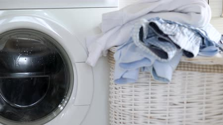 sıkıcı iş : Laundry is washed in the washing machine, and clean things are on the basket nearby. Stok Video