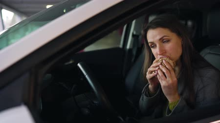 empresária : Woman eating sandwich sitting in the car on the parking. Concept of a modern busy life