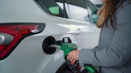 olej : Woman fills petrol into her car at a gas station closeup