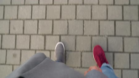 šedé pozadí : Top view of male and female legs strolling along the sidewalk. Woman drinking coffee Dostupné videozáznamy