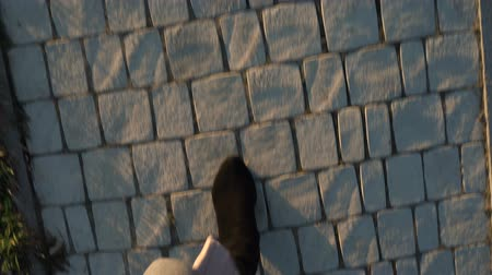 cipő : Top view of female legs in suede boots and pleated skirt walking on the sidewalk