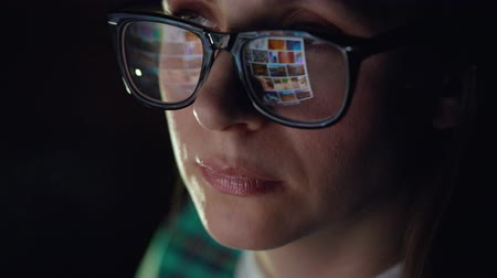 navegar : Woman in glasses looking on the monitor and surfing Internet. The monitor screen is reflected in the glasses Stock Footage