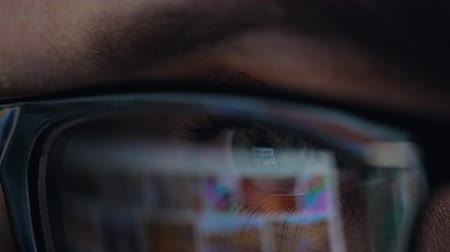 empresária : Woman in glasses looking on the monitor and surfing Internet. The monitor screen is reflected in the glasses Stock Footage
