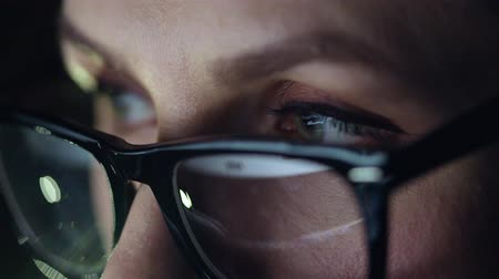 aprender : Woman in glasses looking on the monitor and surfing Internet. The monitor screen is reflected in the glasses Stock Footage