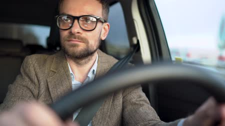 rota : Satisfied bearded man in glasses driving a car down the street in sunny weather Vídeos