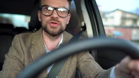 kierowca : Bearded man in glasses drives a car and screaming at someone near him or outside