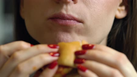 детали : Woman eats a hamburger in a cafe