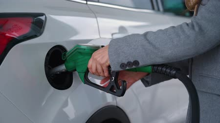 energia : Woman fills petrol into her car at a gas station closeup