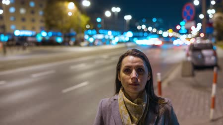 prendas de vestir : Timelapse of woman standing still on crowded evening street while a blur of fast moving cars move behind her