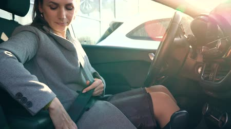 kierowca : Woman fastening car safety seat belt while sitting inside of vehicle before driving